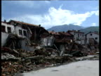 Pan right across destroyed village of Pec returning refugees walk and cycle up road Kosovo 21 Jun 99
