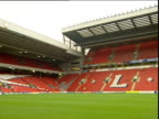 Pan right across football pitch with red seats in stands Anfield football stadium Liverpool