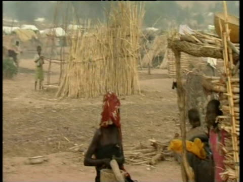 Pan right across makeshift shelters in refugee camp