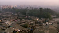 Pan right across rooftops of slum. Available in HD.