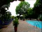 Pan right across swimming pool Chateau Marmont hotel hidden behind trees Sunset Strip Los Angeles