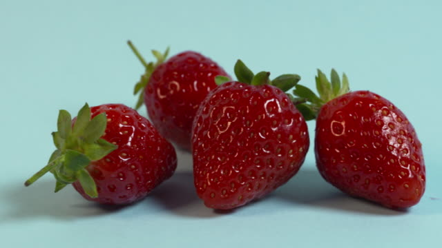 Pan right across, then pan left across, a group of four strawberries arranged on a plain pale blue background.
