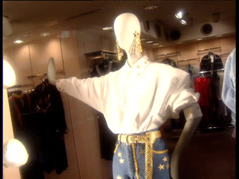 Pan right across two shop mannequins modelling early Nineties fashions USA
