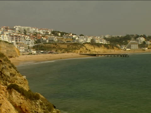 Pan right along Algarve coastline to miles of sandy beach and blue sea whitewashed apartments on hills