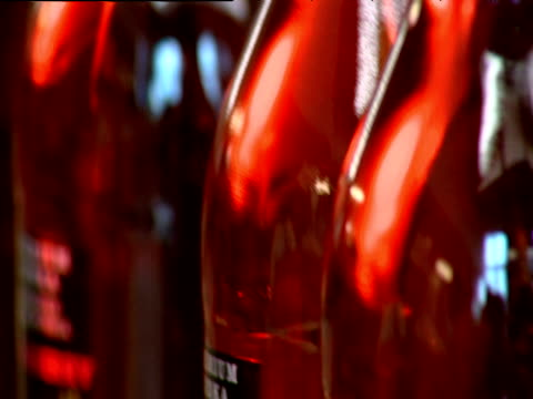 Pan right along bottles of red flavoured vodka in factory Moscow