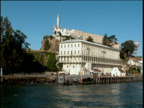 Pan right along exterior of Alcatraz prison against backdrop of blue sky. Windows and balconies set on top of pier like structure with water in foreground.