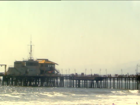Pan right along pier and ferris wheel bathers play and swim in ocean waves Santa Monica State Beach Los Angeles