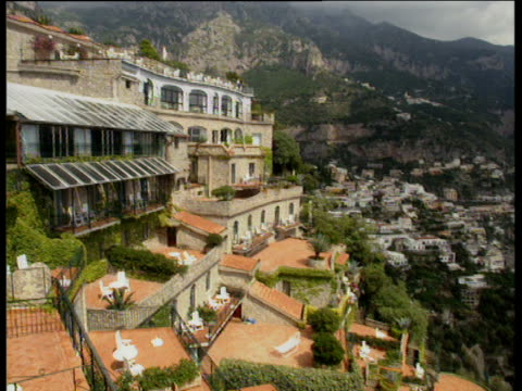 Pan right and tilt down over hotel terraces and swimming pool built into cliff to Mediterranean sea and beaches below