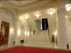 Pan right and tilt up from grand marble staircase to huge chandelier Ceaucescu's Palace world's second biggest building Bucharest