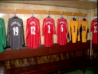 Pan right around Liverpool football players' shirts hanging in Anfield dressing room Liverpool