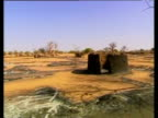 Pan right around wreckage of burned out village during civil war Sudan 2004