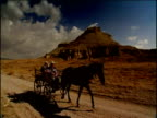 Pan right as elderly couple ride in horse and cart along dusty road Turkey