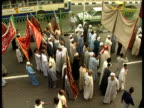 Pan right as Muslim men carry banners in street procession during Maulid festival celebrating birth of Prophet Mohammed Cairo