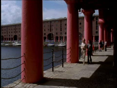 Pan right as people walk next to Royal Albert Dock