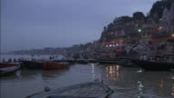 Pan right from boats on Ganges to people watching cremation from boats, Varanasi Available in HD.
