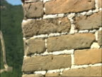 Pan right from bricks, through battlements, to Great Wall of China snaking up hill, Mutianyu, China