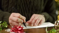 Pan Right From Candy Canes to a Man Putting a Christmas Card in an Envelope