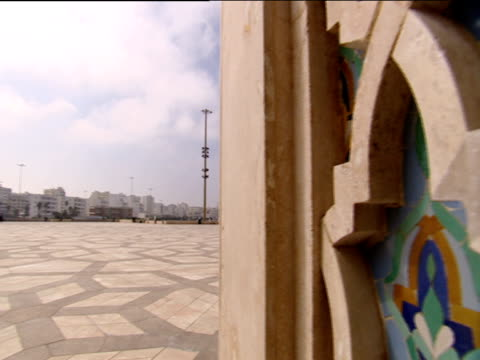 Pan right from paved area to ornate coloured tiling on side of mosque Hassan II Mosque Casablanca
