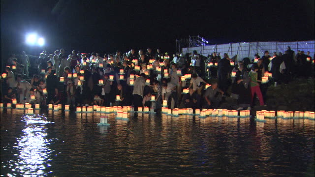 Pan right from people launching lanterns into river from bank to lanterns floating down river (Eiheiji lantern launching rite, a way of seeing off dead spirits), Fukui