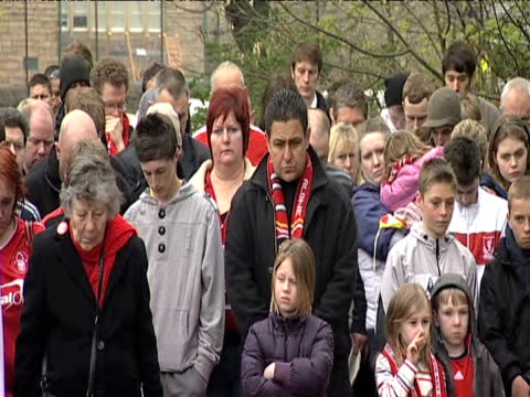 Pan right on group of Liverpool fans holding minutes silence during memorial service marking 20th anniversary of Hillsborough tragedy 15 April 2009