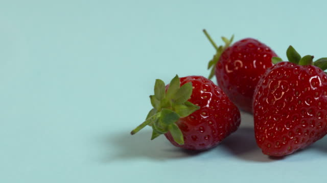 Pan right onto, then off, a group of four strawberries arranged on a plain pale blue background.