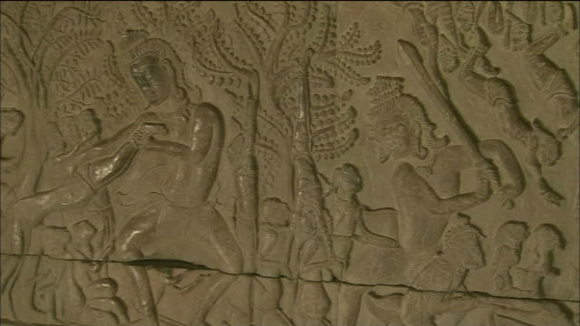 Pan right over carved relief illustrating heaven and hell at Angkor Wat, Cambodia