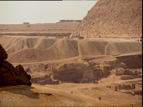 Pan right over desert and ruins to pyramid Egypt