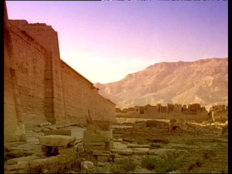 Pan right over Karnak Temple ruins under dusky pink sky