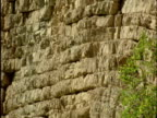 Pan right over limestone cliff showing lines of stratification