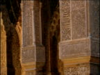 Pan right over ornate carved Moorish pillars in courtyard of Alhambra Palace Spain