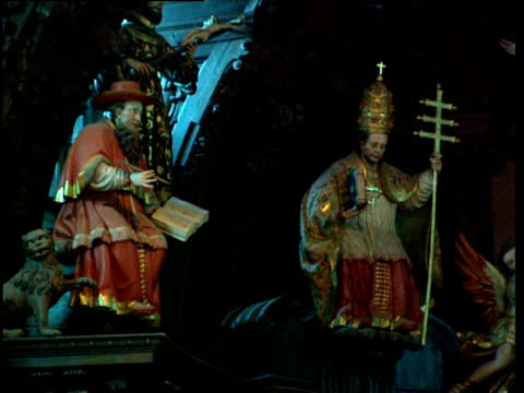 Pan right over ornate statues of Cardinal Pope Mary and Bishops in Catholic church Basque Country Spain