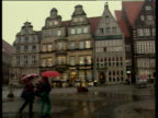 Pan right over town square with cathedral and trams as people with umbrellas walk by