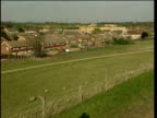 Pan right past houses and fields to large water reservoir
