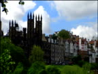 Pan right past houses and trees to Edinburgh Castle on sunny day