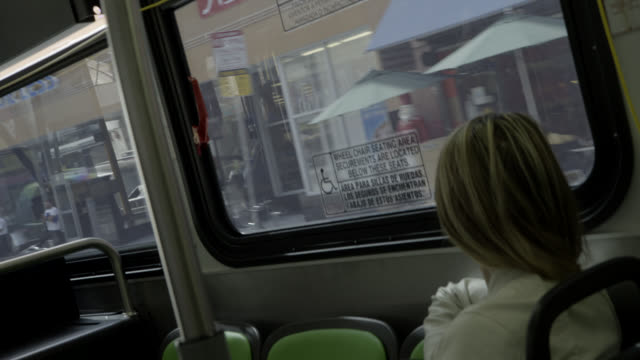 pan right to left moving pov from bus driving through city streets. broadway. passengers.