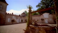 Pan right to well inside courtyard at Chateau d'Yquem / Graves, Bordeaux, France