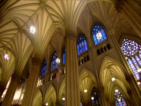 Pan round vaulted ceiling of St Patrick's Cathedral tilt down to congregation at mass New York
