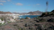 pan shot, agave plants on volcanic hills and sea with white houses