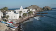 pan shot, fishing boats on sea and shore of small island with white houses