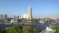 Pan Shot of barge on Chao Phraya River and skyline of Bangkok