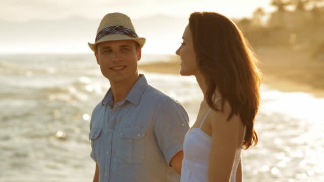 pan shot of young couple walking on beach