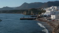 pan shot, people on pier and fishing boats at sea with volcanic hills