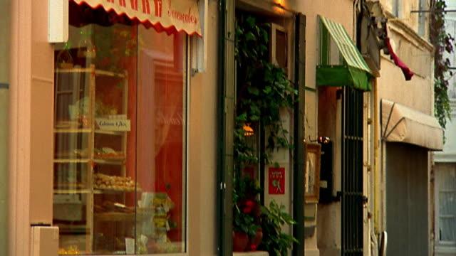 Pan tilt down tilt up store front of bakery (boulangerie) on village street / Provence, France