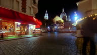 Pan time lapse crowds in Montmartre at night w/Sacre Coeur in background / Paris, France