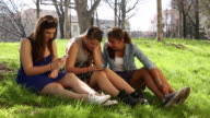 Pan to three teen girls sharing messages from digital technology in urban park
