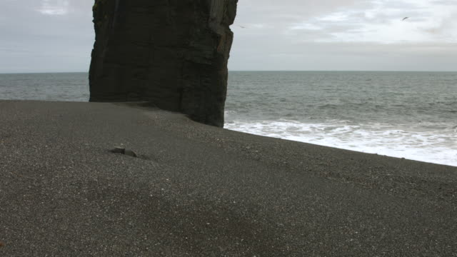 Pan up a basalt rock stack on a beach in southern Iceland.