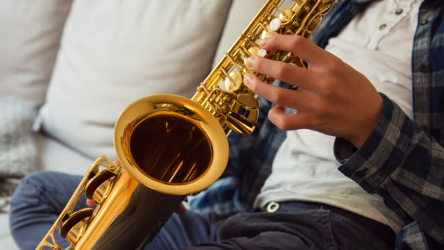 CU pan up, Boy playing saxophone on living room couch