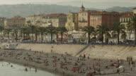 Pan up of people enjoying the Promenade des Anglais / Nice, France