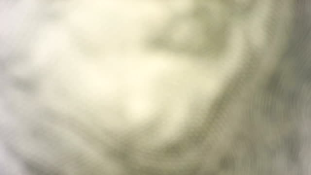 Pan up to a close up of Benjamin Franklin's face on the hundred dollar bill