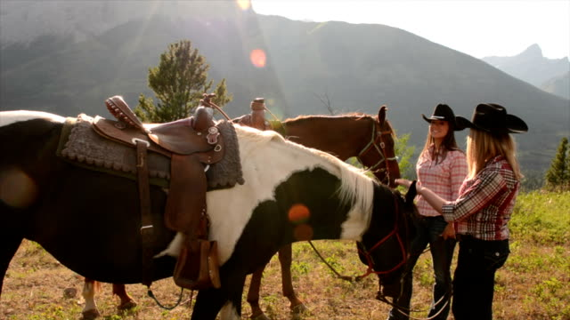 Pan up to women with horses in mountain meadow